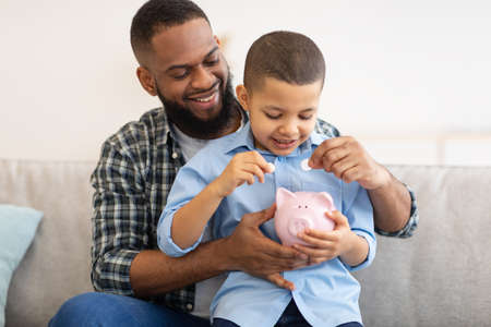 African American Daddy And Son Putting Coin In Piggybank Indoor