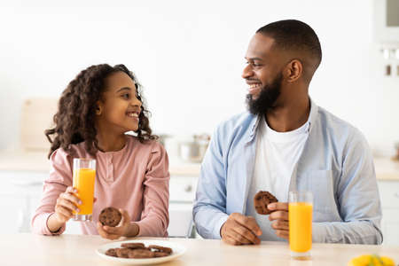 Cheerful african american daughter and dad having breakfast Imagens