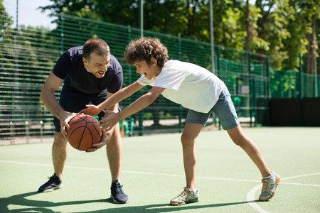 Sportive man teaching boy how to play basketball outside