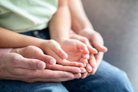 Closeup Shot Of Mom, Dad And Child Placing Their Hands Together