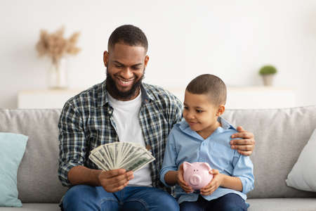 Dad Holding Money Talking With Son About Personal Savings Indoor