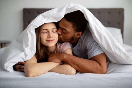 Romantic black guy kissing his Caucasian girlfriend under blanket on bed, indoors