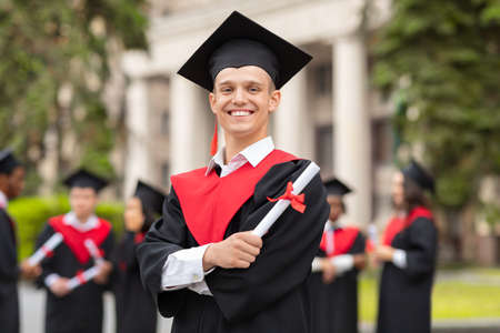 Cheerful guy in graduation costume with diploma posing outdoors