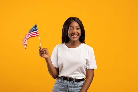 Positive black woman student holding american flag