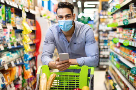 Arabic Male Customer With Smartphone Doing Grocery Shopping In Supermarket