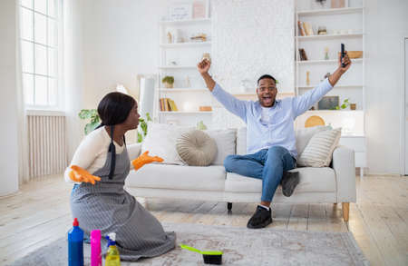 Excited black guy watching football on TV, happy over victory of his team, angry offended wife cleaning house alone