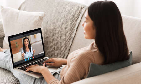 Online Tutoring Concept. Young Asian Female Having Virtual Lesson With Female Tutor Banque d'images