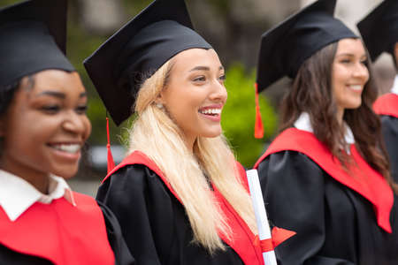 Pretty blonde lady standing among international group of students