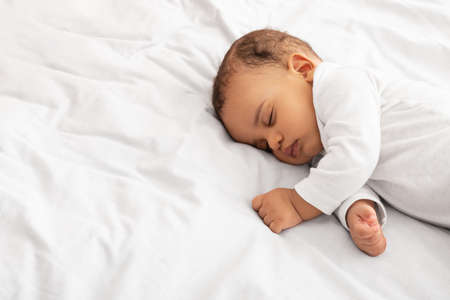 Little Baby Boy Sleeping Peacefully Lying In Bed Indoors
