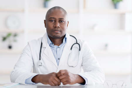 Portrait of confident african american doctor in white uniform looking seriously at camera, free space Foto de archivo
