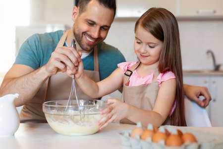 Cheerful Father And Daughter Cooking Pancakes Making Dough In Kitchen