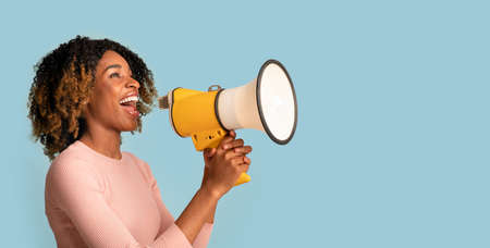 Announcement Concept. Cheerful Black Woman Shouting With Megaphone In Hands, Blue Background Standard-Bild