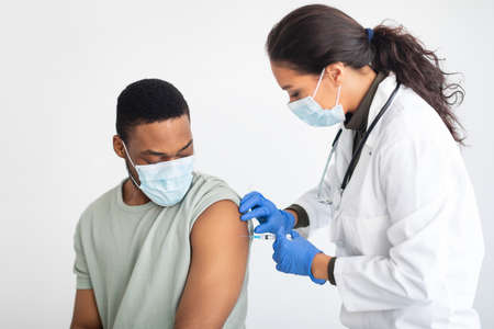 General Practitioner Vaccinating African American Male Patient Over White Background