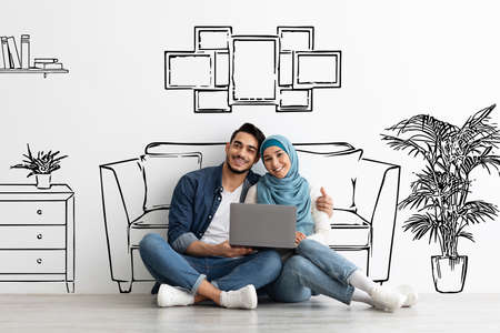 Happy muslim family sitting on floor with laptop