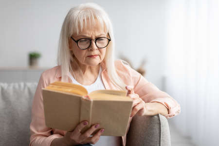Focused mature woman in glasses trying to read book