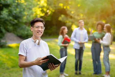 Study Abroad Programs. Happy Asian Guy With Workbook In Hands Posing Outdoors