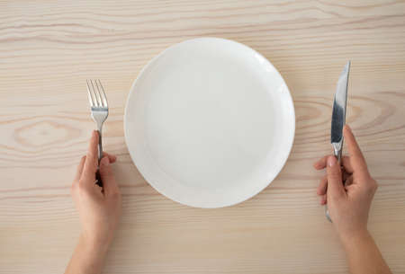 White empty plate and female hands holding silver fork and knife on wooden table background, top view