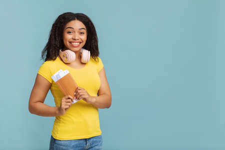 Travelling concept. Joyful african american lady with headphones holding tickets on blue studio background, free space Reklamní fotografie