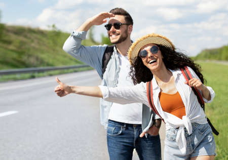 Happy young coupe flagging down car, needing ride, hitchhiking on roadside outdoors