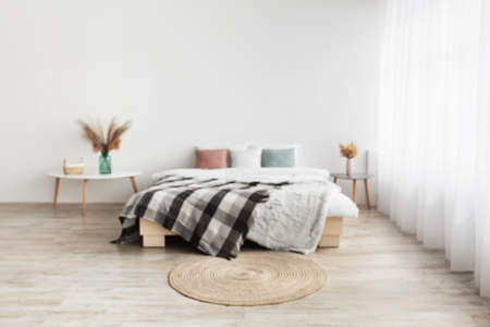 Blog about home interiors and cozy design. Double bed with pillows and blanket, tables with dry plants in vases