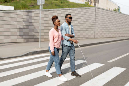 Young black woman assisting visually impaired millennial guy with cane crossing city street. Vision disability concept