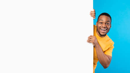 Excited African American Man Posing With White Poster, Blue Background