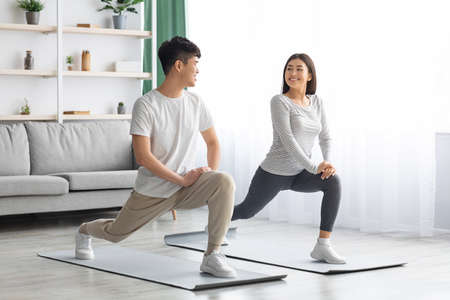 Happy asian couple exercising at home, copy space