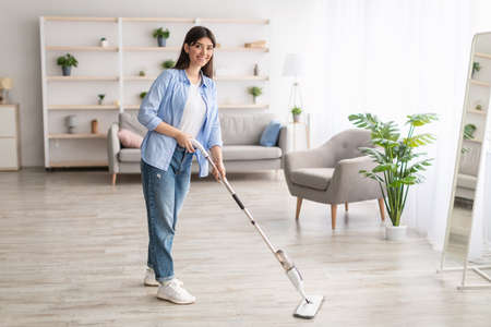 Portrait of cheerful woman cleaning floor with spray mop