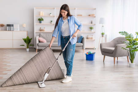 Portrait of woman cleaning floor in living room using mop Banque d'images