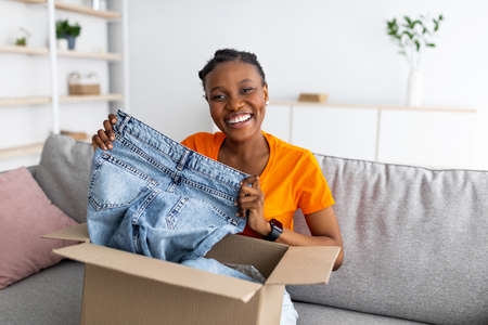 Happy black woman holding jeans, unboxing cardboard package, receiving ordered product, satisfied with her purchase