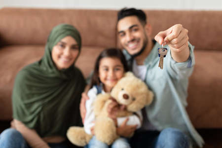 Happy arabic family showing keys of their apartment