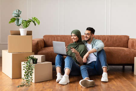 Happy man and woman using laptop after relocation