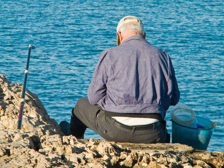 fishingline: People: A Fisherman sitting on a rock at Polignano town in Apulia.