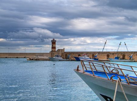 prow: Tourism: This is a panoramic view with lighthouse and close-up of a boat prow at Monopoli seafront, in Apulia. Stock Photo