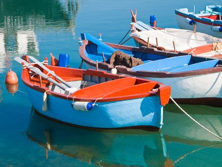rowboat: Transport: These are a colored rowboats in clear sea.