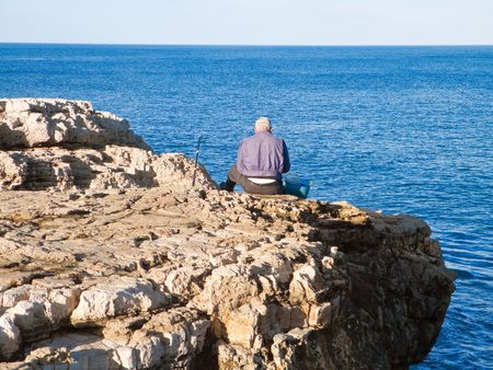 fishingline: People: This is a fisherman sitting on the rocks.