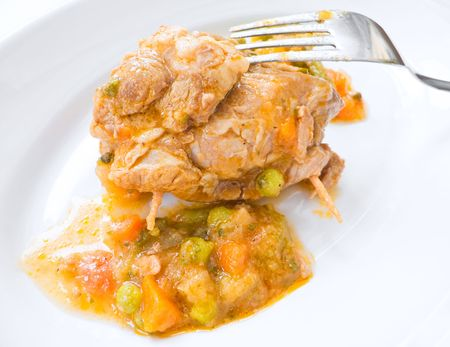 Food: This is a meat roulade with vegetable soup on white dish.  photo