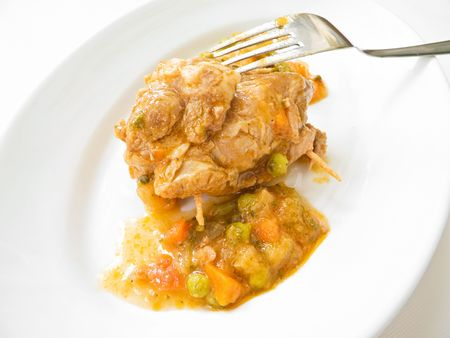 Meat roulade with vegetable soup on white dish.  photo