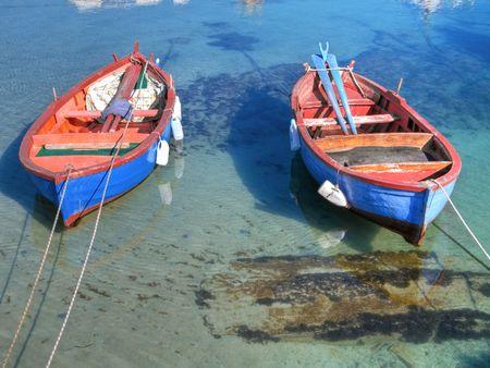 Coloured rowboats in clear sea in Giovinazzo . Apulia. photo
