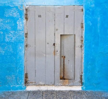scraped: Wooden door on blue wall.