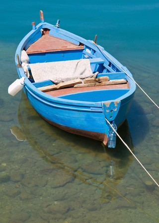 rowboat: Coloured rowboat in clear sea.