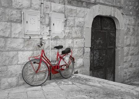 Red bicycle leaning against wall. photo