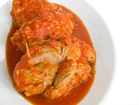 Meat roulade in tomato sauce on white dish. photo