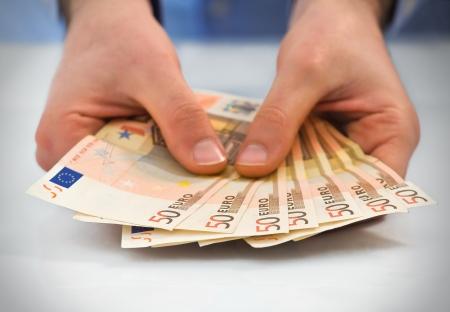 remuneraciones: Manos con pila de cincuenta billetes en euros. Foto de archivo