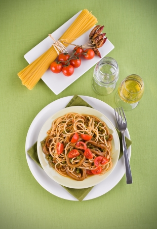 Spaghetti with squids, peas and cherry tomatoes. photo