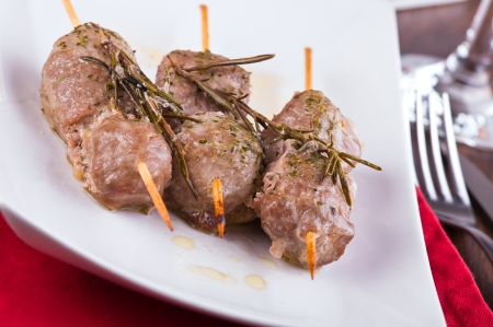 Meat skewers on white dish. photo