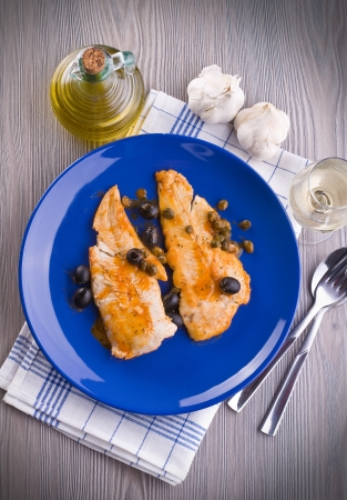 Fish fillet with black olives and capers   photo