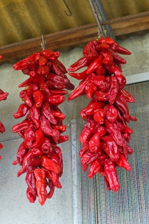 valsinni: Red hot peppers hanging on the wall  Stock Photo
