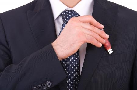 Businessman putting usb stick in his pocket.