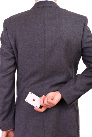 Businessman holding playing card behind his back  photo